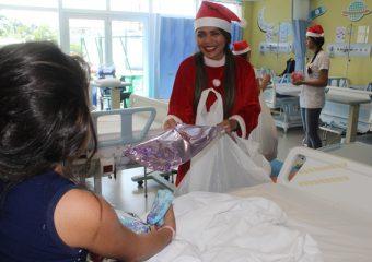 Ao som do Coral de Colaboradores, Papai Noel entrega presentes às crianças internadas